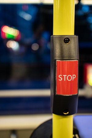 obscured: Extreme close up of red stop request button on yellow pole for public bus with obscured seat and window in background