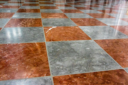 low angles: Red and white marble floor with alternating colored stone tiles viewed at a low angle with oblique perspective Stock Photo