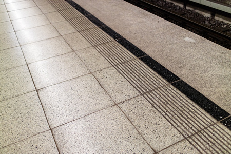 hardwearing: Image of speckled subway flooring with black trim and safety markings near train tracks