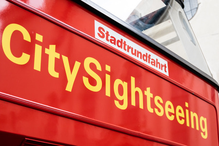 equivalent: Colorful red City Sightseeing signboard with yellow text below the German equivalent in a tourism and travel concept