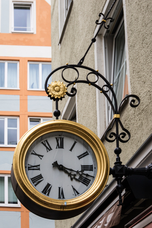 bracket: Low angle view on large outdoor clock with Roman numerals attached to building with decorative wrought iron bracket Stock Photo