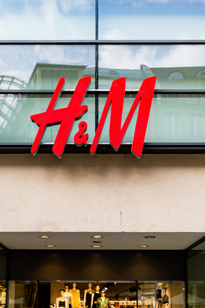 clothed: Street level view of H and M lighted storefront with fashionably clothed mannequins Editorial