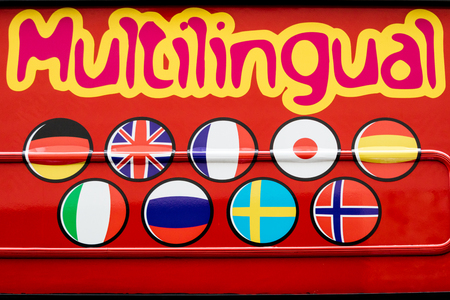 multilingual: Eye-catching red Multilingual sign with round icons depicting a diverse selection of international flags for languages spoken
