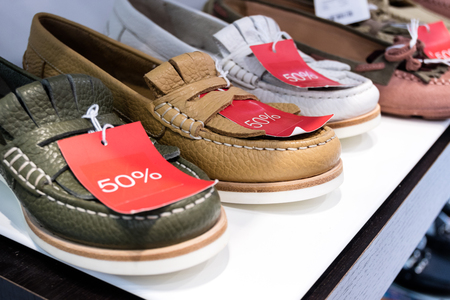 moccasin: Leather moccasin shoes on sale in a store with red discount price tags with a 50 percent reduction