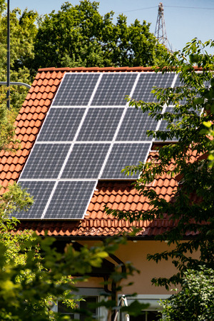 converting: Installation of photovoltaic solar energy panels mounted on a house roof for converting solar energy to electricity as a sustainable resource
