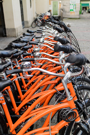 parking facilities: Row of identical orange bicycles parked in an urban bicycle rack for hire for sightseeing and commuting Stock Photo