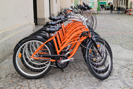 handle bars: Row of identical orange bicycles parked in an urban bicycle rack for hire for sightseeing and commuting Stock Photo