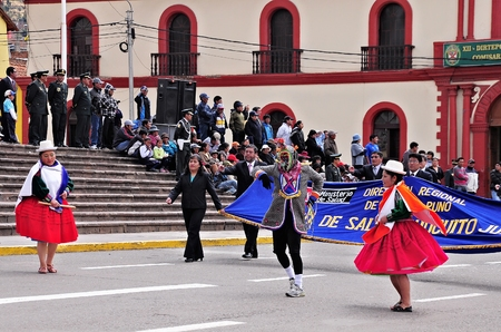 Women and men dressed in national costumes go over the main city square as they arrive at the parade on May 19, 2013 in Puno, Peru