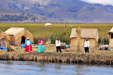 Local people greet visitors in the floating village of Uros islands on Lake Titicaca on May 20, 2013, Peru