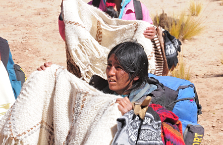 Woman-indian sells clothes during the train stop in Andes on April 27, 2013, Argentina  Altitude approx  is 4000 m above sea level