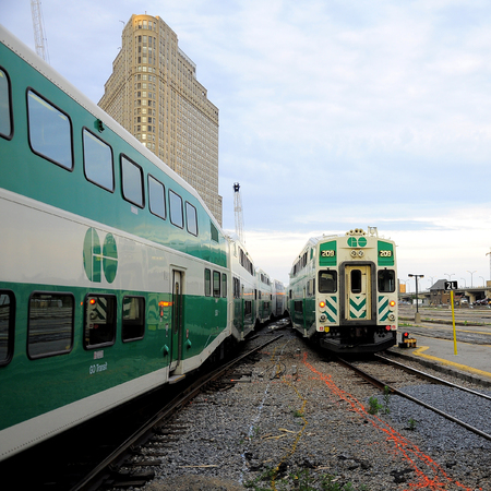 suburbian: First passenger train  on the left  arrives, second passenger train  on the right  departs from Toronto Union station on June 27, 2011 in Toronto, Canada