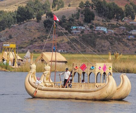 Indians sail by the handmade boat to Uros island on Lake Titicaca on May 20, 2013, Peru