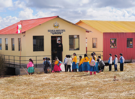 Group of unidentified children and teacher stand by the school in the morning in the floating village of Uros islands on Lake Titicaca on May 20, 2013, Peru