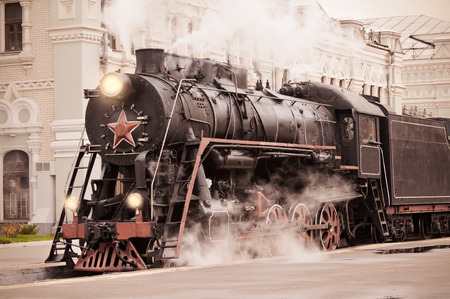 Retro steam train stands on the railway station