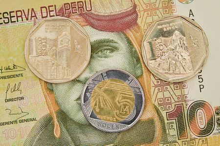 Peruvian coins on ten soles banknote background   photo