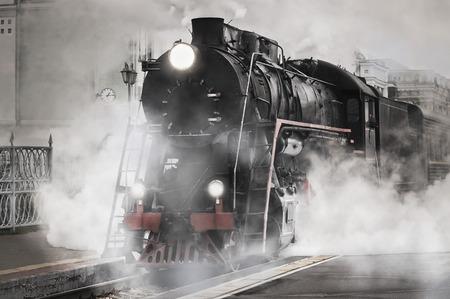 レトロな蒸気機関車鉄道駅から出発します。 写真素材