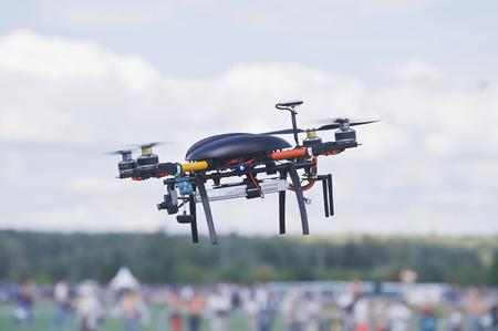 人々 の群衆の上の黒い quadrocopter。
