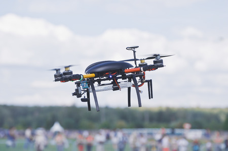 Black quadrocopter above the crowd of people. Stock Photo