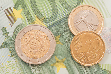 one hundred euro banknote: Euro coins on one hundred euro banknote background.