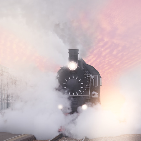 peron: Retro steam train departs from the railway station at sunset.