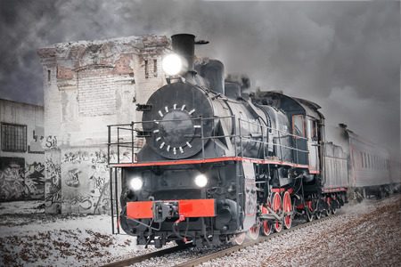 Retro steam train goes fast on the abandoned buildings background. photo