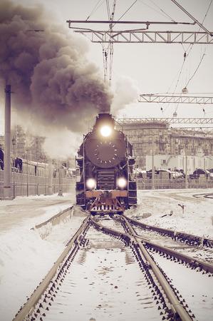 レトロな蒸気機関車は、日没に鉄道駅から出発します。ビンテージ イメージ。