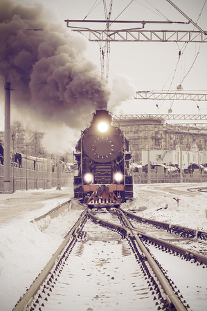 Retro steam train departs from the railway station at sunset. Vintage image.