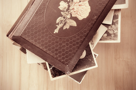 photoalbum: Old photo-album with retro pictures inside it on wooden background.