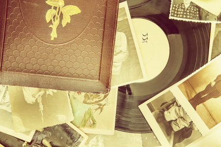 photoalbum: Old photo-album with retro pictures and black vinyl record on the table.