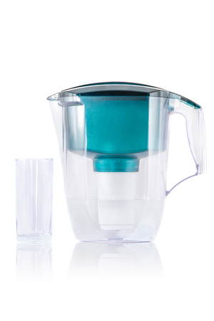 purifying: Green water filter and glass with theirs reflection on white background.