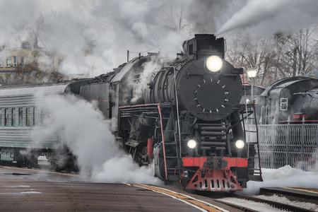 레트로 증기 기차는 저녁 시간에 기차역에서 출발합니다. 스톡 콘텐츠