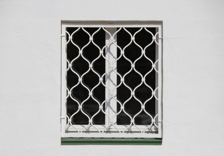 penal institution: Closed window in the old building on sunny day.