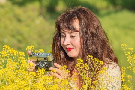 Woman shooting flowers on the meadow with vintage photo camera.