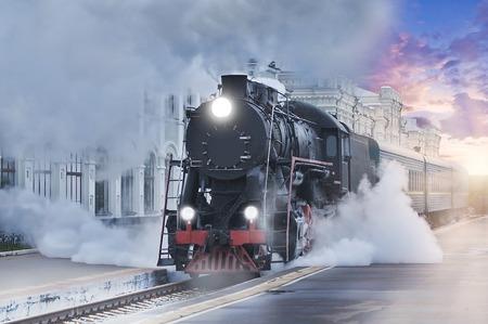 レトロな蒸気機関車は、日没に鉄道駅から出発します。