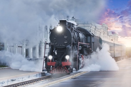 Retro steam train departs from the railway station at sunset.