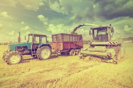 agricultura: Máquinas agrícolas recogen heno en el campo en un día de verano. Foto de archivo