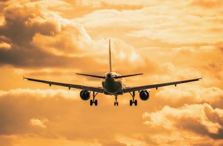 aeroplanes: Landing of the passenger plane at sunset time. Stock Photo