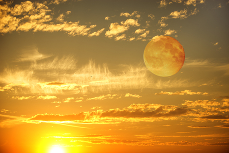 golden light: Evening sunset sky with the colorful clouds and moon.