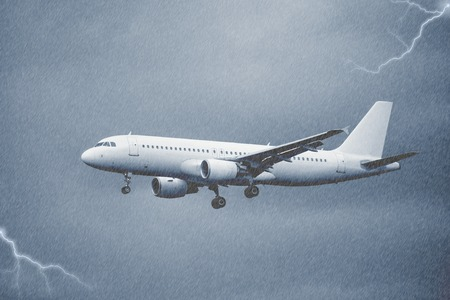 Landing of the passenger plane under the pouring rain. Stock Photo