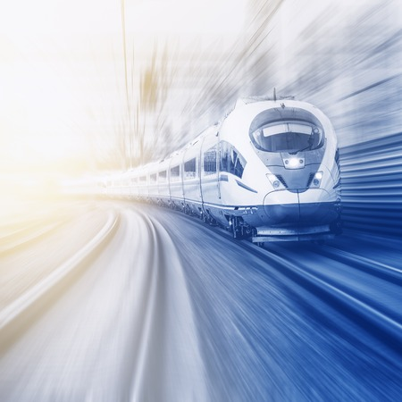 Modern high-speed train moves fast at sunset time.