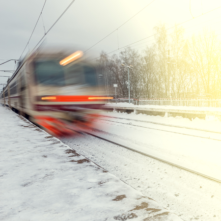 treno espresso: High-speed train arrives to the station at winter evening time. Archivio Fotografico
