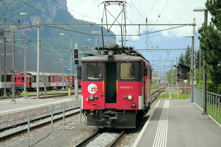 interlaken: Meiringen, Switzerland - July 03, 2012: The retro electric locomotive moves toward the carriages of the train to Interlaken.