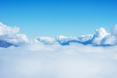 aerial: Clouds above the mountains at day time. Stock Photo