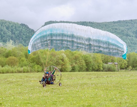 taking off: Guama, Russia - May 04, 2015: Taking off the paraglider with passenger and instructor from the meadow.