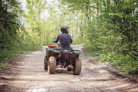El hombre en el ATV Quad en el camino de las montañas.