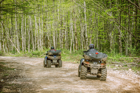 atv: Guama, Russia - May 03, 2015: Two men on the ATV Quad Bikes on the mountains road. Editorial