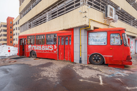 outside machines: Korolev, Russia - March 01, 2016: Exterior of the beer bar made from the retro soviet Liaz bus inside of the garage building.