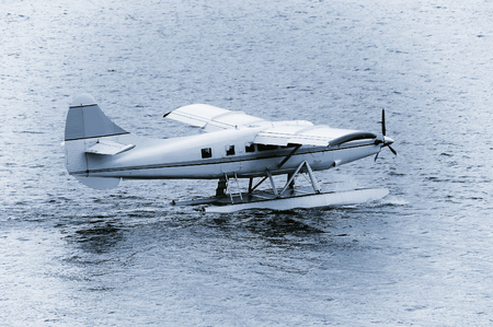 taking off: Taking off the small passenger plane from the water surface. Stock Photo