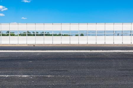 ruido: Parte de la nueva carretera con valla de protección contra el ruido a lo largo.
