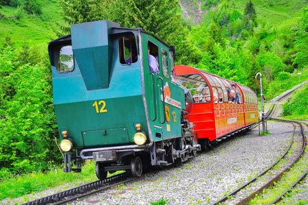 narrow gauge: Planalp, Switzerland - June 12, 2010: Train from Rothorn to Brienz arrives to the station. Brienz-Rothorn bahn is cogwheel narrow gauge railway with beautiful mountain views.